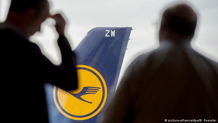 Two men observe a Lufthansa plane at the airport in Frankfurt