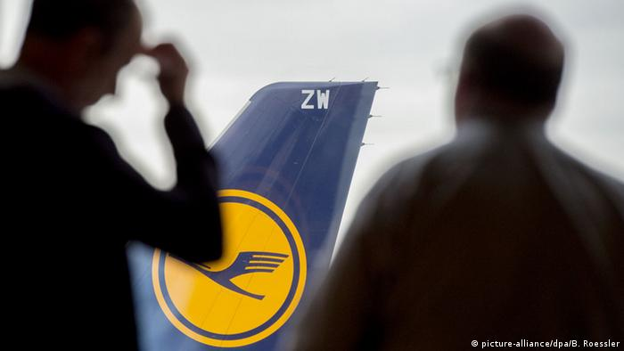 Passengers look at a grounded Lufthansa plane at Frankfurt airport