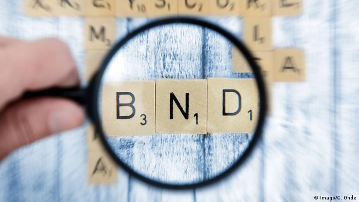 Человек держит увеличительное стекло над буквами B, N и D