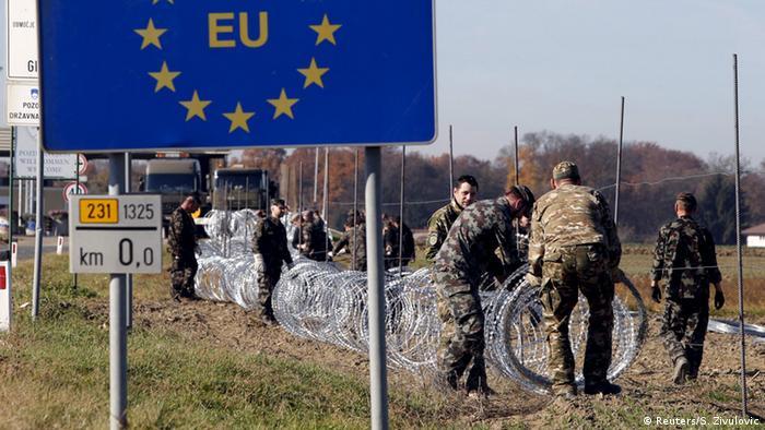 Soldaţi sloveni ridică un gard de sârmă ghimpată la frontiera cu Croaţia