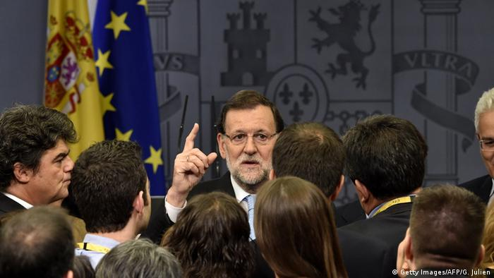 Prime Minister Mariano Rajoy (C) speaks to journalists at the end of a press conference.
