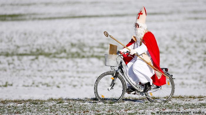 Nikolaus mit Stab und Mitra fährt auf Fahrrad über verschneite Wiese, Deutschland (dpa)