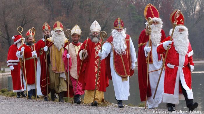 Verschiedene Nikolaus-Darsteller in einer Reihe unterwegs