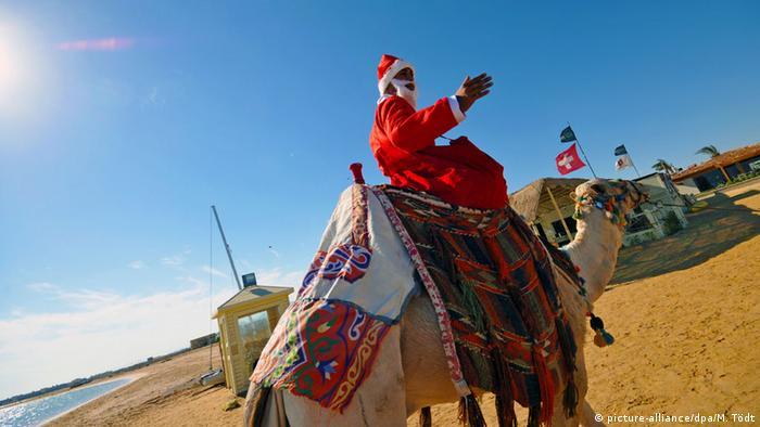 Auf einem Dromedar reitet ein Hotelangestellter im Nikolauskostüm am Strand des Roten Meeres in Ägypten