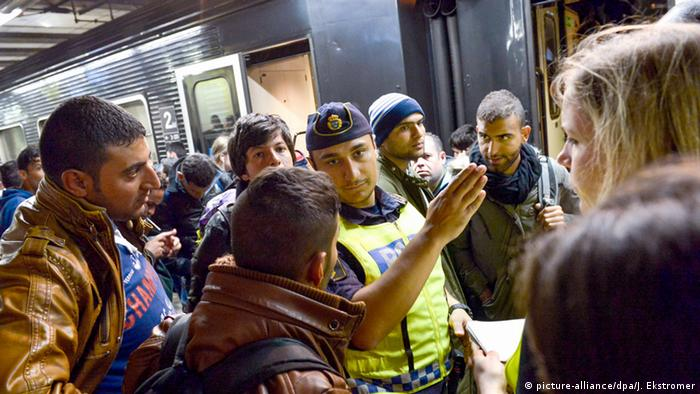 Migrants get directions from a policeman at a train station in Stockholm in 2015