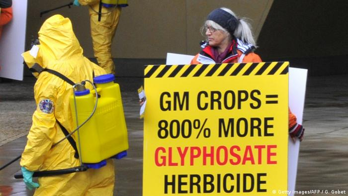 "Protesters display a banner reading ""GM crops = 800% more glyphosate herbicide"" outside the Commission headquarters in 2012"