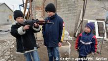 Ostukraine Donezk Region Kinder spielen mit Waffen