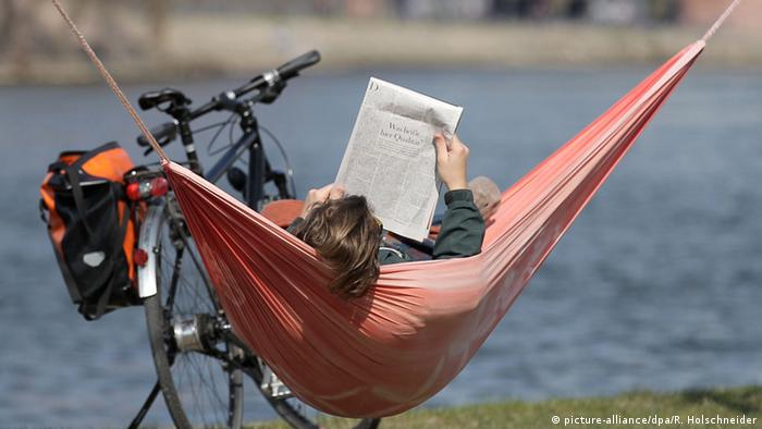 Man with a newspaper in a hammock, Copyright: picture-alliance/dpa/R. Holschneider