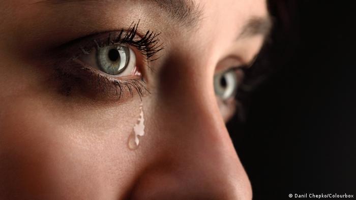 Imagem de uma lágrima caindo no rosto de uma mulher