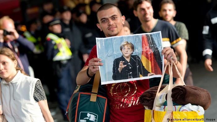 Ein Flüchtling, der kurz zuvor mit einem Zug angekommen ist, läuft am 05.09.2015 auf dem Hauptbahnhof in München (Bayern) über den Bahnsteig und hält dabei ein Foto von Angela Merkel in den Händen - Foto: Sven Hoppe (dpa)