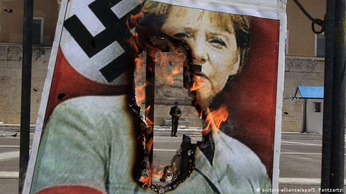 A protest poster in front of the Greek parliament, depicting Angela Merkel dressed in Nazi uniform