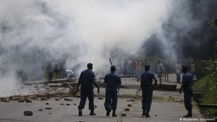 Burundian policeman look at a white cloud of tear gas fired at protestors