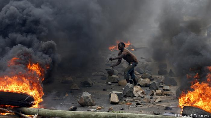 A protester in Bujumbura amid rubble and fires