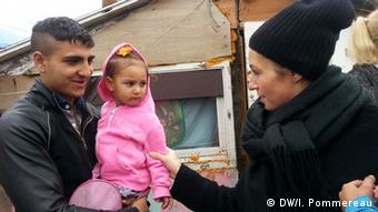 Olimpia Swist stands with a Roma man and small girl at a Roma settlement in Wroclaw