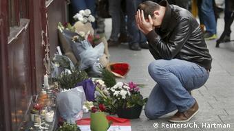 Цветы приносят к тем местам, где были совершены нападения. На фото: мужчина у ресторана Le Carillon
