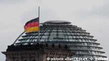 The German Reichstag building with a flag flying at half-mast