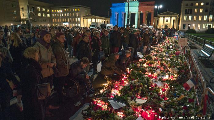 Акция у Бранденбургских ворот. Люди возлагают цветы и зажигают свечи у посольства Франции.