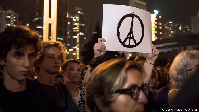 Weißes Peace-Schild mit Eiffelturm in der Mitte wird aus einer Menschenmenge hochgehalten. (Getty Images/X. Olleros)