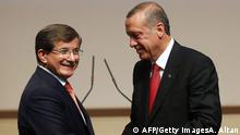 Turkey's president-elect Recep Tayyip Erdogan (R) shakes hands with Turkey's Foreign Minister Ahmet Davutoglu after he announced Davutoglu as new chairman of his ruling Justice and Development Party (AKP) and new Turkish prime minister in Ankara on August 21, 2014. Davutoglu, named by the AKP as its sole candidate to be new leader and prime minister, is a loyal ally of his predecessor, incoming president Recep Tayyip Erdogan, and the chief architect of an assertive but increasingly controversial foreign policy. He will take office on August 28. AFP PHOTO / ADEM ALTAN (Photo credit should read ADEM ALTAN/AFP/Getty Images) Subscription-Download