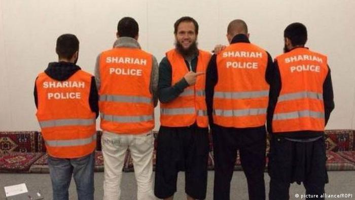 """Příslušníci takzvané """"šaríjské policie"""" v oranžových vestách"""