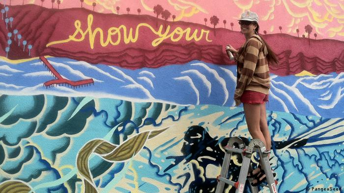 An artist on a ladder in front of a finished mural of the ocean