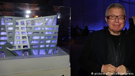 Daniel Libeskind in front of a model of a futuristic building.