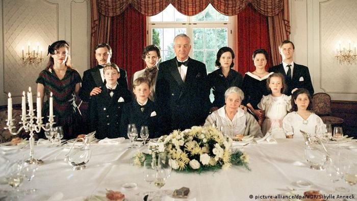 Die Manns - Filmstill - anlässlich des Geburtstags von Katia Mann (Monica Bleibtreu) versammelt sich die Familie Thomas Manns (Armin Mueller-Stahl) hinter dem gedeckten Tisch für ein Familienfoto