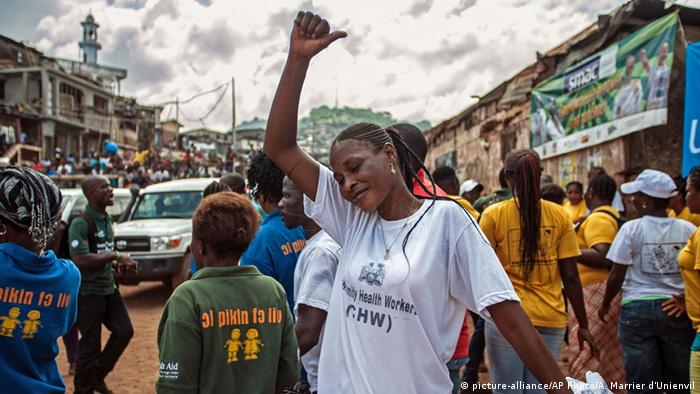 A woman with an outstretched fist among people celebrating as Sierra Leone is declared Ebola free in 2015 (picture-alliance/AP Photo/A. Marrier d'Unienvil)
