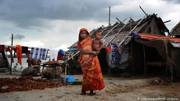 A woman stands with a child in one of Dhaka's 5,000 slums