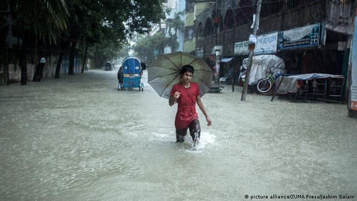 A boy wades through tidal flooding in Chittagong, Bangladesh (picture alliance/ZUMA Press/Jashim Salam)