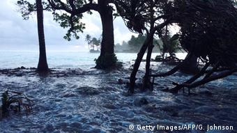 A high tide washes across an atoll that makes up the Marshall Islands