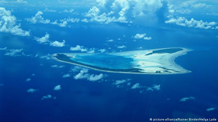 An aereal photo of an atoll in the ocean