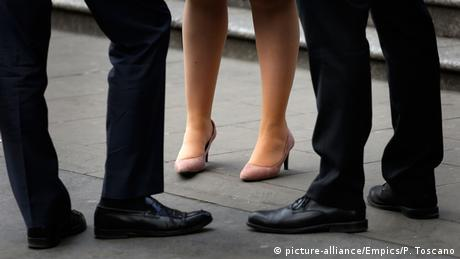 Three pairs of legs: two with black trousers and shoes, one with tights and pink high heels (picture-alliance/Empics/P. Toscano)