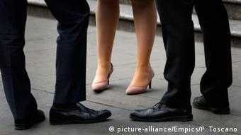 Legs and feet of two men and a woman standing together