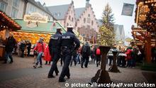 ARCHIV - Zwei Polizeibeamte laufen am 04.12.2014 auf dem Weihnachtsmarkt in Frankfurt am Main (Hessen) Streife. Foto: Fredrik von Erichsen/dpa (zu lhe Mit Lautsprecher und Streifen: Sicherheit auf dem Weihnachtsmarkt vom 18.11.2015) +++(c) dpa - Bildfunk+++ picture-alliance/dpa/F.von Erichsen