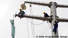 27.7.2015 *** Bildunterschrift:Chinese engineers from PowerChina and Sinohydro work on a building site of a high-voltage power line on July 27, 2015 in the district of Yopougon in Abidjan. AFP PHOTO / ISSOUF SANOGO (Photo credit should read ISSOUF SANOGO/AFP/Getty Images) Copyright: Getty Images/AFP/I. Sanogo