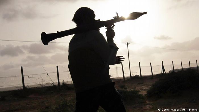 Silhouette of an African militiaman wielding a grenade propeller