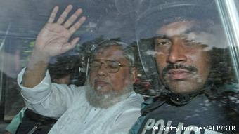 Secretary General of Jamaat e Islam, Ali Ahsan Mohammad Mujahid (L) waves from a police vechile as he is transported to the central jail following his court verdict in Dhaka on July 17, 2013 (Photo: Getty Images/AFP/STR)