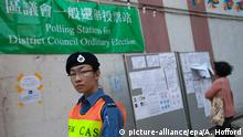 22.11.2015*** epa05037247 A Civil Aid Service officer standing guard outside a polling station in Choi Wan South in Wong Tai Sin District during Hong Kong's District Council elections, Ping Shek Estate, East Kowloon, Hong Kong, China, 22 November 2015. Due to a surge in young people registering to vote in the post-Occupy Central / Umbrella Movement political landscape, voter turnout this year's District Council election has been higher than in 2007 and 2011. EPA/ALEX HOFFORD +++(c) dpa - Bildfunk+++