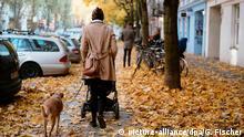 28.10.2015 *** Eine Frau läuft am 28.10.2015 mit Kinderwagen und einem Hund an der Leine auf einem Gehweg in Berlin über herbstlich gefärbtes Laub. Foto: Gregor Fischer/dpa Copyright: picture-alliance/dpa/G. Fischer