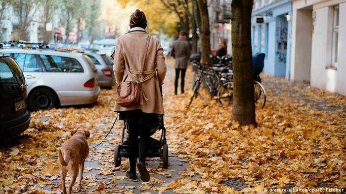 Women with dog and stroller walking through leaves in the city (picture-alliance/dpa/G. Fischer)