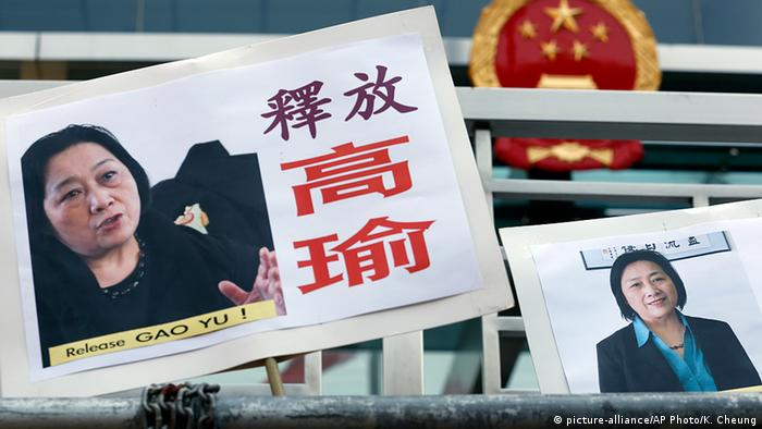 In this April 17, 2015 file photo, pictures of jailed veteran Chinese journalist Gao Yu are displayed by protesters outside Chinese central government's liaison office in Hong Kong.