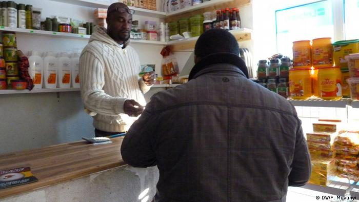 An African shopkeeper and customer in a shop in Germany