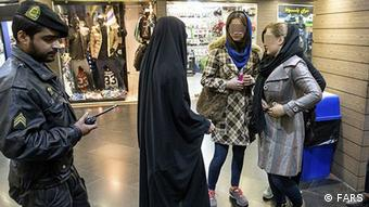 A vice squad policeman in Tehran stops women for improper clothing
