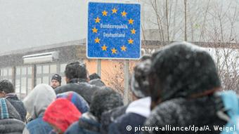 Migrants wait to cross the border into Germany