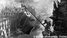 ARCHIV - Der sowjetische Soldat Militon Kantarija aus Georgien hisst am 2. Mai 1945 die sowjetische Flagge auf dem Berliner Reichstag. Deutschland hatte den Zweiten Weltkrieg verloren. Foto: dpa +++(c) dpa - Bildfunk+++ Copyright: picture-alliance/dpa/J. Chaldej