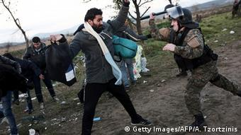 Macedonian policeman hits a refugee with his baton