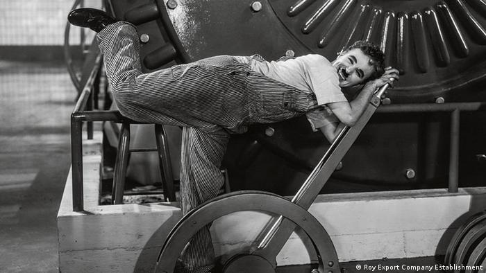Charlie Chaplin cavorting over a giant lever and cog