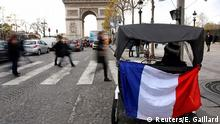 26.11.2015 **** A French national flag hangs from a tricycle on the Champs Elysees Avenue near the Arc de Triomphe in Paris, France, November 26, 2015. The French President called on all French citizens to hang the tricolour national flag from their windows on Friday to pay tribute to the victims of the Paris attacks. REUTERS/Eric Gaillard Foto: Reuters/E. Gaillard