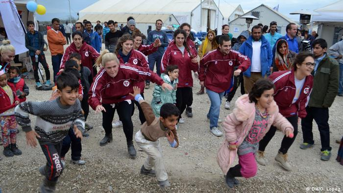 Volunteers play with children at Idomeni refugee camp
